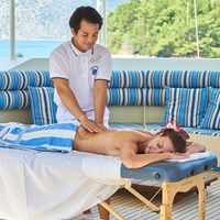 guest having massage on the table on ship deck