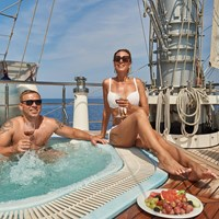 guests in jacuzzi with wine and fruits