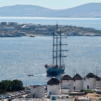 ship next to Mykonos coast and town windmills