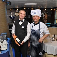 chef and waiter in the restaurant with wine bottle