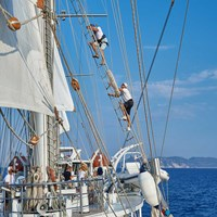 guest climbing mast above crew member