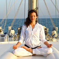yoga instructor on ship top deck in a pose