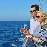 guests on the ship looking at sea holding champaigne glasses