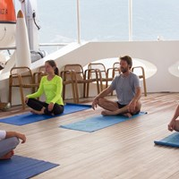 yoga class on the mats on the sun deck of the ship