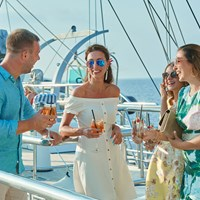guests dressed with cocktails on the ship top deck