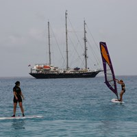 guests windsurfing near ship