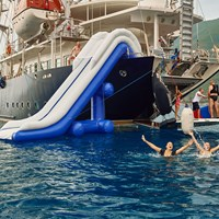 guests swimming next to ship with water slide and open apparel