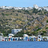 coastal island town with white houses and rocky hills